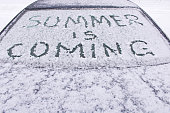 The inscription soon the summer on the frozen glass of the car .