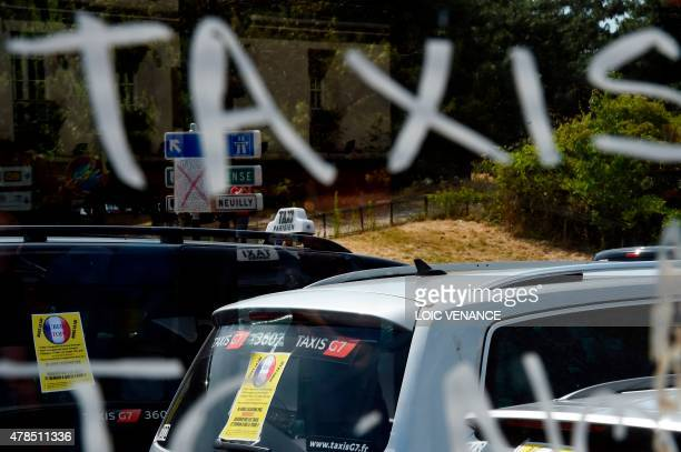 The inscription 'Taxis' is tagged onto a car window as taxi drivers stage a demonstration/blockade at the Porte Maillot traffic roundabout on June 25...