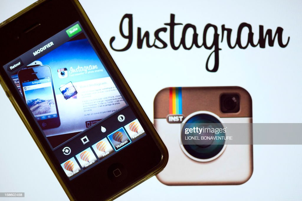 The Instagram logo is displayed next to a smartphone on December 20, 2012 in Paris. Instagram backed down on December 18, 2012 from a planned policy change that appeared to clear the way for the mobile photo sharing service to sell pictures without compensation, after users cried foul. Changes to the Instagram privacy policy and terms of service set to take effect January 16 had included wording that appeared to allow people's pictures to be used by advertisers at Instagram or Facebook worldwide, royalty-free. AFP PHOTO / LIONEL BONAVENTURE