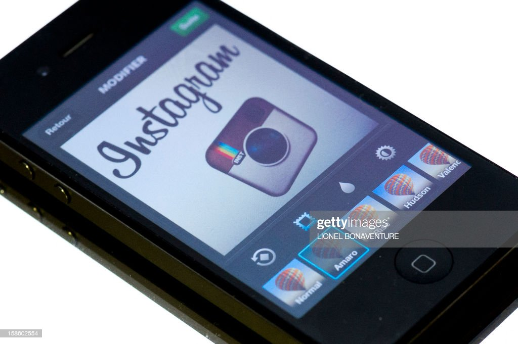 The Instagram logo is displayed on a smartphone on December 20, 2012 in Paris. Instagram backed down on December 18, 2012 from a planned policy change that appeared to clear the way for the mobile photo sharing service to sell pictures without compensation, after users cried foul. Changes to the Instagram privacy policy and terms of service set to take effect January 16 had included wording that appeared to allow people's pictures to be used by advertisers at Instagram or Facebook worldwide, royalty-free. AFP PHOTO / LIONEL BONAVENTURE