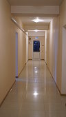The interior corridor with door for exit in the end. The position of the room door is opposite the corridor.