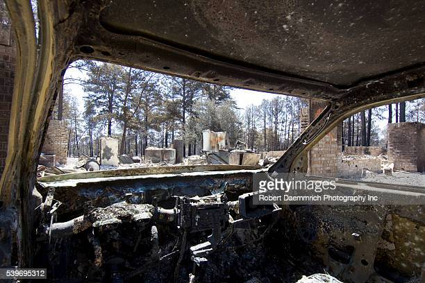 The interior of a burned out car with a flattened house shows the aftermath of wildfire through the piney woods in Bastrop County 30 miles east of...