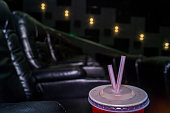 The interior of a modern cinema hall for watching movie, show and entertainment program. The auditorium is equipped with black leather seats. The theater is empty, it does not show the film and there