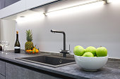 The interior of the modern kitchen is illuminated with a gray stone countertop with a luxury washbasin and mixer, fruit pineapple and tangerines, a bottle with red wine and two glasses.