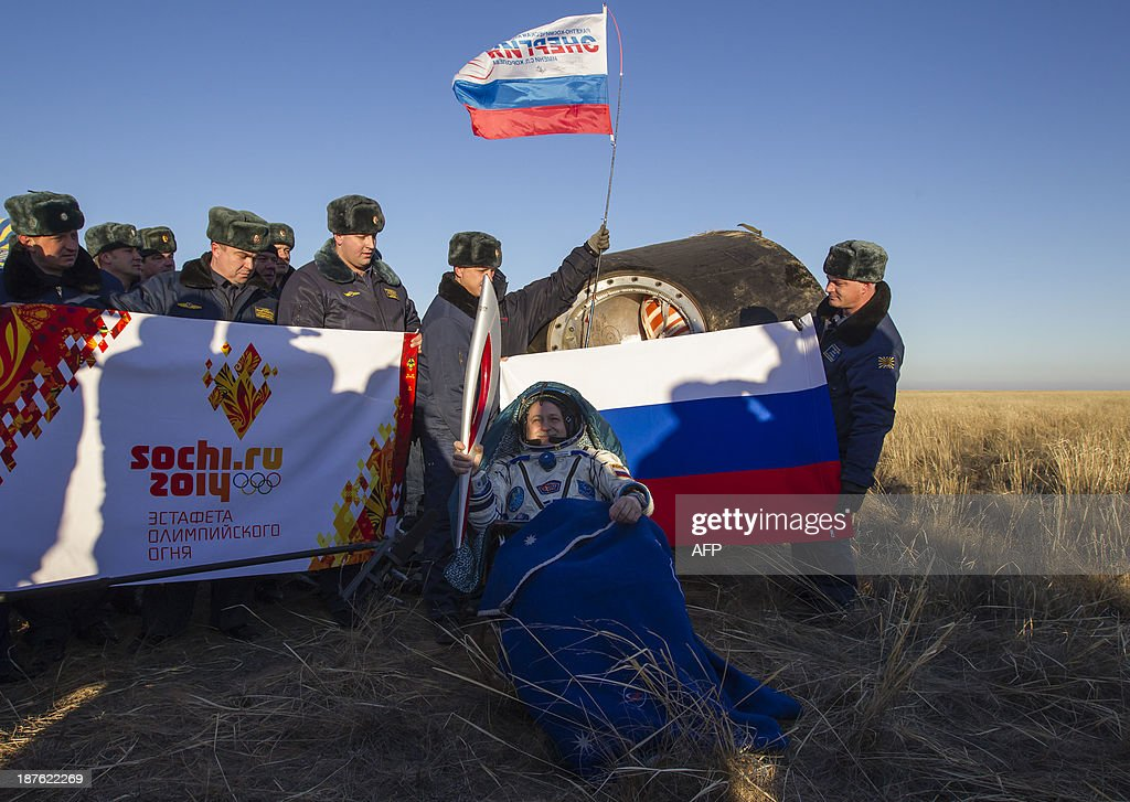 The International Space Station (ISS) crew member Russian cosmonaut Fyodor Yurchikhin holds the torch of the 2014 Sochi Winter Olympic Games after landing near the town of Zhezkazgan in central Kazakhstan on November 11, 2013. The three astronauts returned to Earth, after 66 days aboard the International Space Station, bringing back the Olympic torch back to the planet after a historic space walk. AFP PHOTO / POOL Shamil Zhumatov