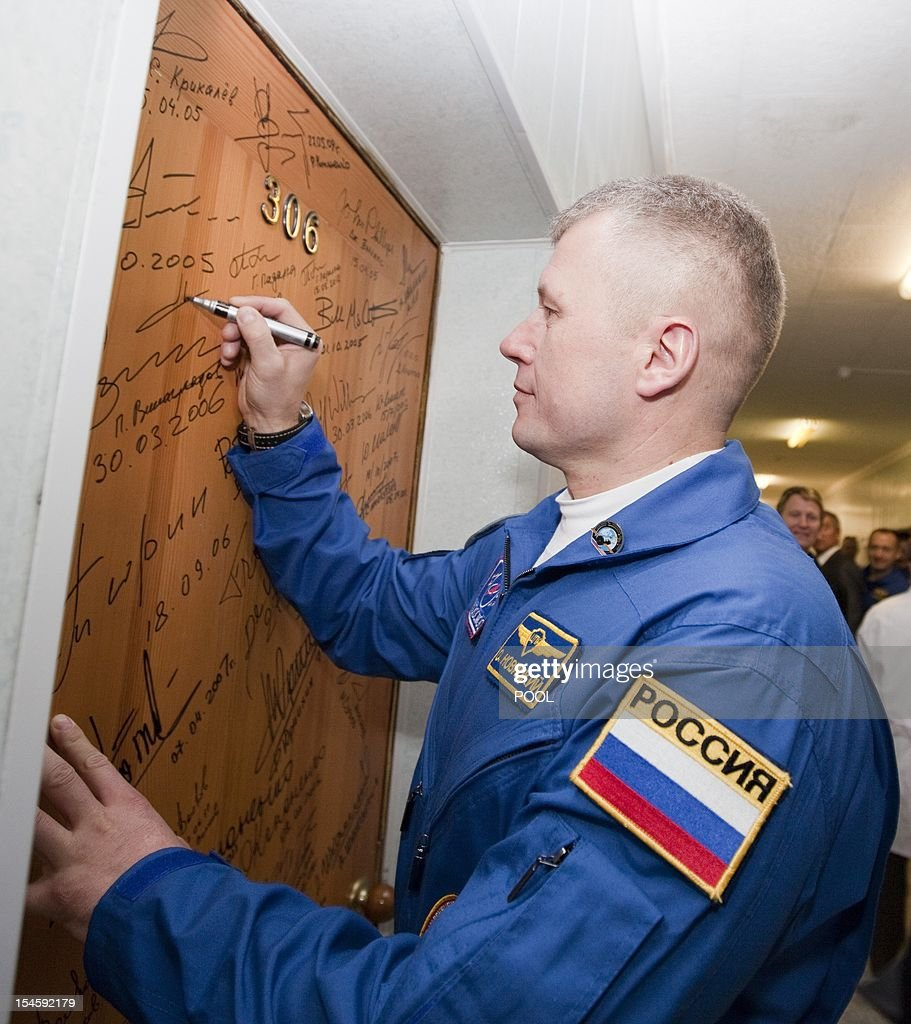 The International Space Station (ISS) crew member Russian cosmonaut Oleg Novitskiy signs a door of a hotel before leaving for a final pre-launch preparation at the Baikonur cosmodrome October 23, 2012. AFP PHOTO / POOL / Sergei Remezov