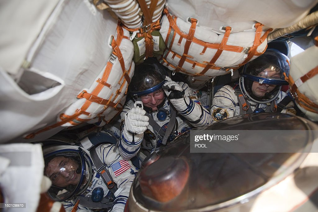The International Space Station (ISS) crew members, US astronaut Joseph Acaba (L), Russian cosmonauts Gennady Padalka (C) and Sergei Revin sit inside the Soyuz TMA-04M capsule shortly after its landing near the town of Arkalyk in northern Kazakhstan, on September 17, 2012. A woman took today command of the ISS for only the second time as three US and Russian colleagues made a safe return from the orbiting space lab to the Kazakh steppe. AFP PHOTO / POOL/ SERGEI REMEZOV