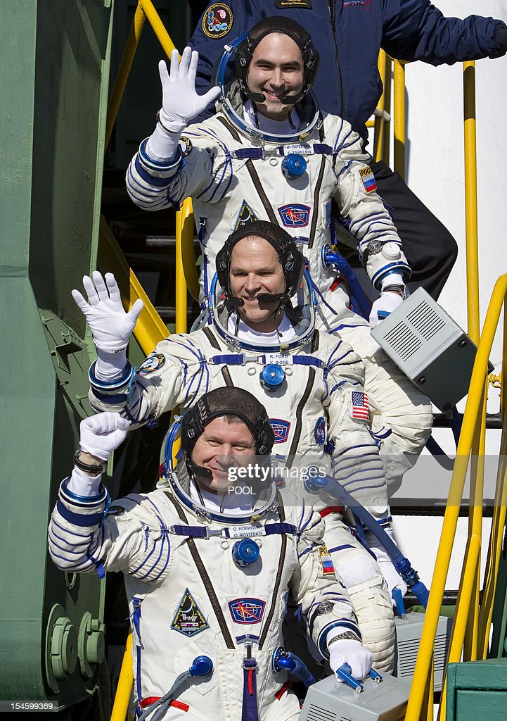 The International Space Station (ISS) crew members, US astronaut Kevin Ford (C) and Russian cosmonauts Oleg Novitskiy (bottom) and Evgeny Tarelkin (top) wave as they board the Soyuz TMA-06M spacecraft at the Russian leased Kazakhstan's Baikonur cosmodrome, on October 23, 2012, shortly before their launch.