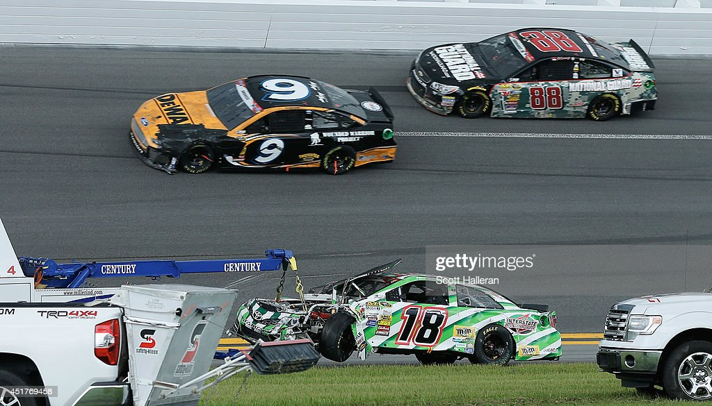 The #18 Interstate Batteries Toyota, driven by Kyle Busch, is towed from the track after an incident during the NASCAR Sprint Cup Series Coke Zero 400 at Daytona International Speedway on July 6, 2014 in Daytona Beach, Florida.