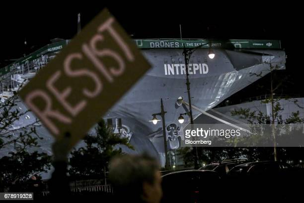 The Intrepid Sea Air Space Museum stands beyond a sign held by a demonstrator during a protest in New York US on Thursday May 4 2017 President Donald...