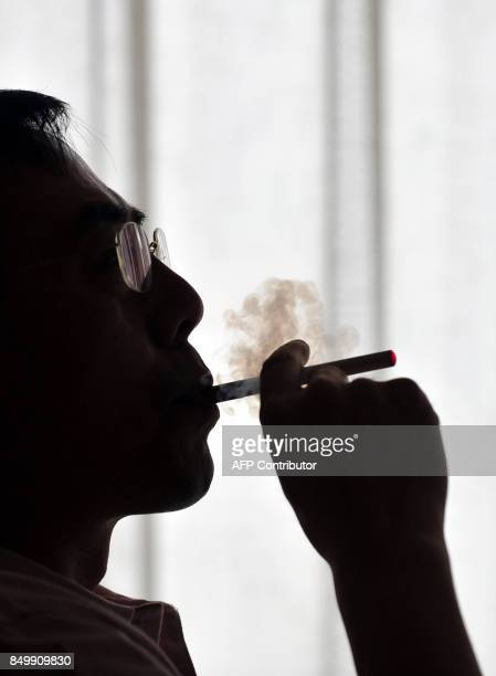 The inventor of the electronic cigarette Hon Lik smokes his invention in Beiijng on May 25 2009 Also known as an 'ecigarette' the batterypowered...