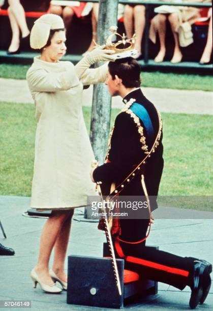 The Investiture of The Prince of Wales at Caernarvon Castle on July 1 1969 Prince Charles kneels before the HRH Queen Elizabeth II as she places the...