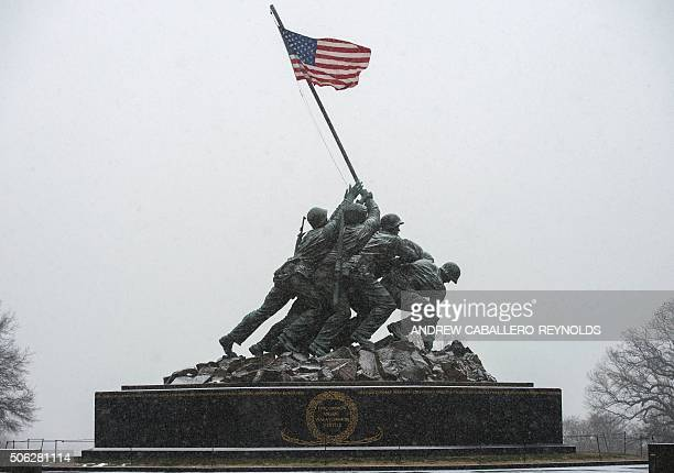 The Iowa Jima memorial is seen during a snow storm in Arlington Virginia on January 22 2016 Thousands of flights were cancelled and supermarket...
