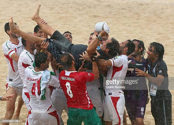 The Iran coach is raised in the air after winning the Men's Beach Soccer gold medal match between Iran and Japan during the 2014 Asian Beach Games at...