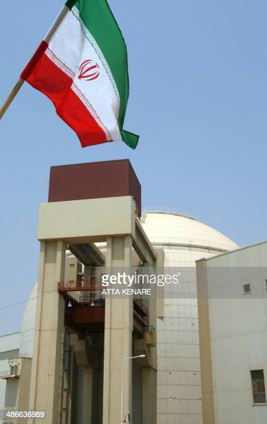 The Iranian flag flutters over the reactor building at the Russianbuilt Bushehr nuclear power plant in southern Iran on August 21 2010 during a...