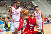 The iranian power forward Hamed Hadadi defends against a drive to the basket by The mexican point guard Jorge Ivan Gutierrez in the match between...