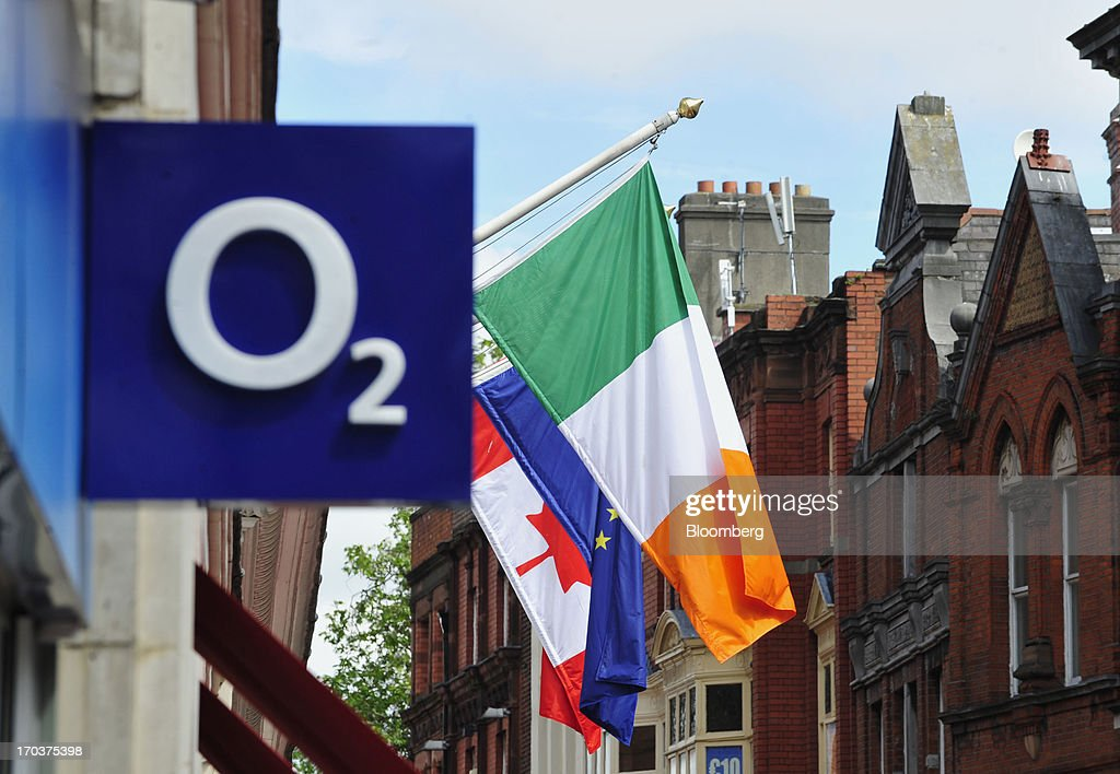 The Irish flag, right, European Union (EU) flag, center, and Canadian flag fly outside an O2 Mobile Phone Store, part of Telefonica SA, on Grafton Street in Dublin, Ireland, on Wednesday, June 12, 2013. Telefonica SA, Europe's most indebted telephone company, is seeking initial bids for its Irish unit within the month, two people with knowledge of the matter said. Photographer: Aidan Crawley/Bloomberg via Getty Images