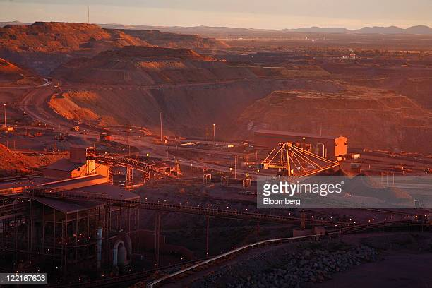 The iron ore excavation pit and processing machinery are seen in evening sunlight at Sishen open cast mine operated by Kumba Iron Ore Ltd an iron...