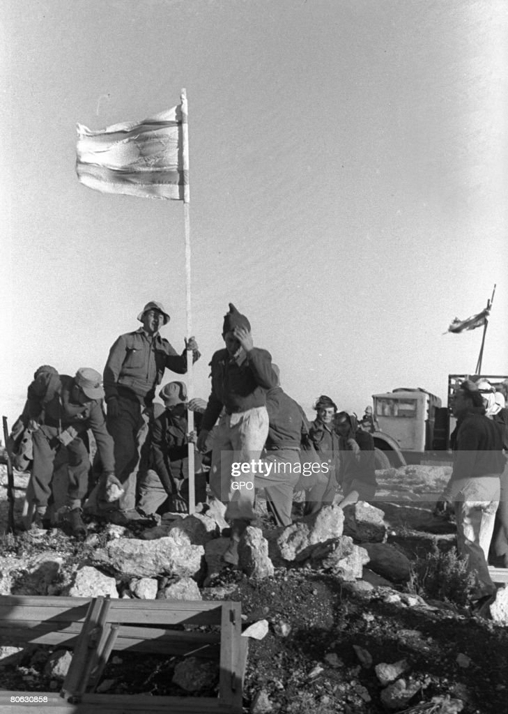 The Israeli flag is raised as pioneer immigrants from Europe establish January 1, 1949 the cooperative farming community of Kibbutz Yasur in the Galilee in northern Israel.