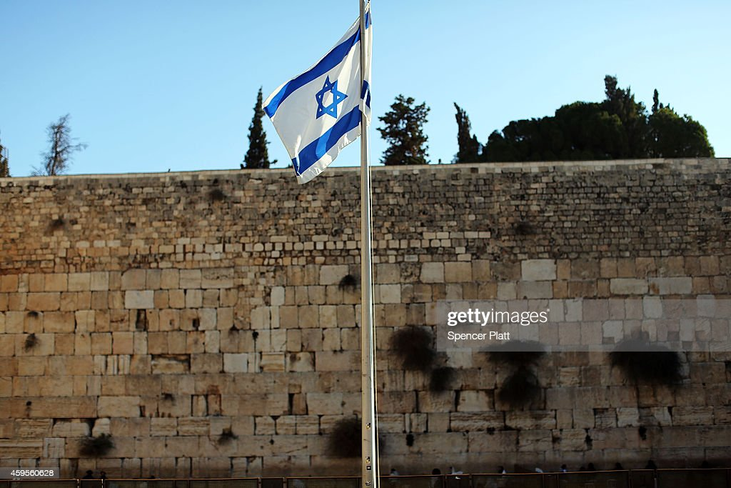 The Israeli flag is viewed near the Western Wall in the the Old City on November 25 2014 in Jerusalem Israel Nine Israelis have been killed in a...