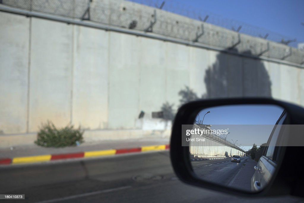 The Israeli West Bank barrier is seen in a rearview mirror on the outskirts of Jerusalem on September 12, 2013 in Aram, West Bank. The twenty-year anniversary of the Oslo Accord, which was to set up a framework for peace between Israel and Palestine, will be marked on September 13.