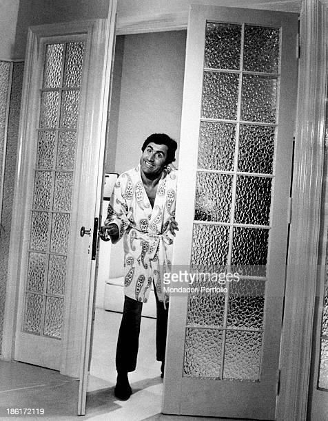The Italian actor Lando Buzzanca is appearing at a glass door in a scene of the film La Schiava io ce l'ho e tu no directed by Giorgio Capitani...