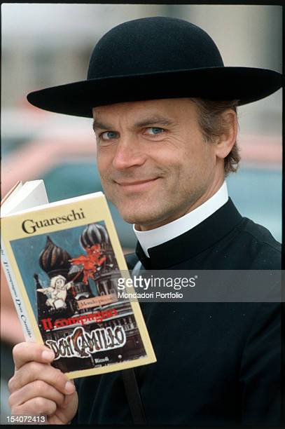 The Italian actor Terence Hill in the role of Don Camillo holding the novel by Giovannino Guareschi that inspired the character he played Italy 1983