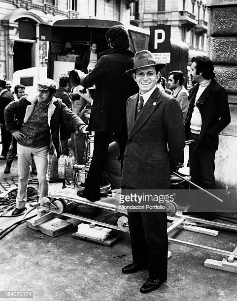 The Italian actor Umberto Orsini smiling on the set of the film The Assassination of Matteotti Behind him the operators are preparing the set for the...