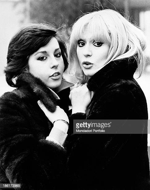 The Italian actress and singer Daniela Goggi is posing upright in front of her older sister the singer actress and show girl Loretta two years ago...