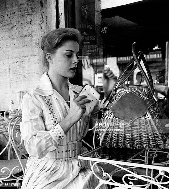The Italian actress Virna Lisi who became famous for a commercial about a toothpaste is putting her wallet in her wicker bag while seated at an...