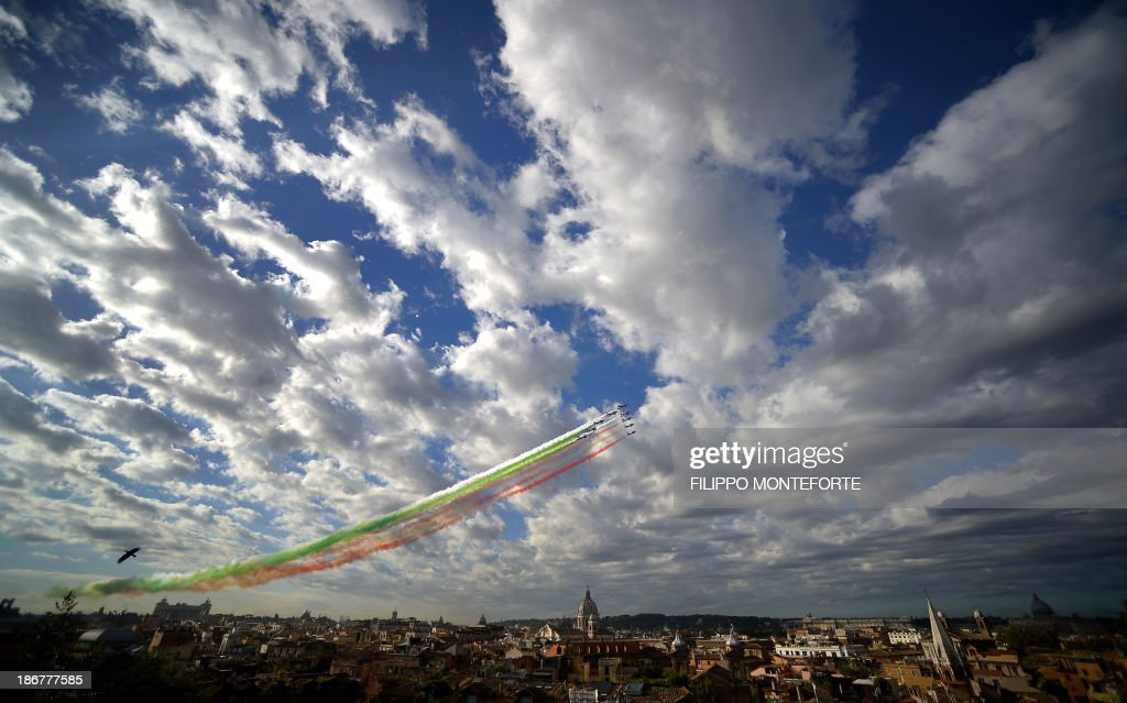 The Italian Air Force aerobatic unit Frecce Tricolori spreads green, white and red smoke in the colours of the Italian flag marking the day of National Unity and Armed Forces in Rome on November 4, 2013. AFP PHOTO/Filippo MONTEFORTE