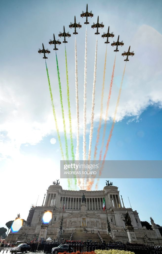 The Italian Air Force aerobatic unit Frecce Tricolori spreads smoke with the colors of the Italian flag over the Piazza Venezia during the armed...