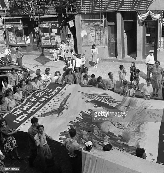 The Italian American neighbors of Mott Street in New York City hold a flag raising ceremony in honor of the local boys who are entering the US Army...