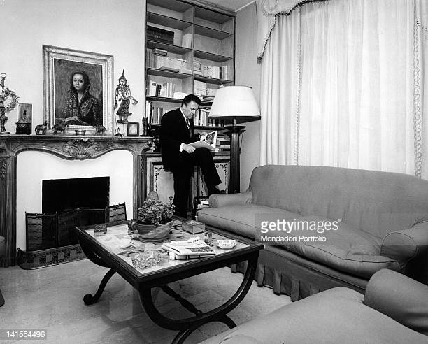 The Italian director Federico Fellini reading a book in the living room of his home Rome 1962