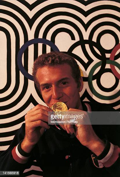 The Italian diver Klaus Dibiasi is celebrating his victory in the Olympic final race of 10 metre platform He is kissing the gold medal behind him the...