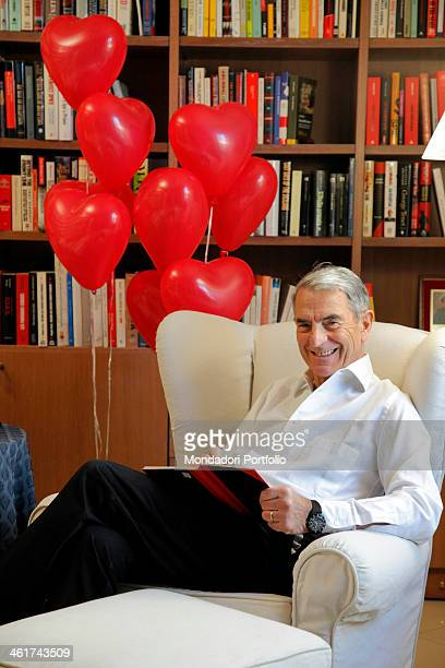 The Italian journalist Carlo Rossella poses smiling in his home with a book and some heartshaped baloons Pavia 9th March 2012