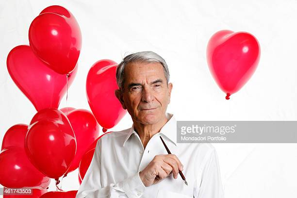 The Italian journalist Carlo Rossella poses thoughtful with a pen and some heartshaped baloons Pavia 9th March 2012