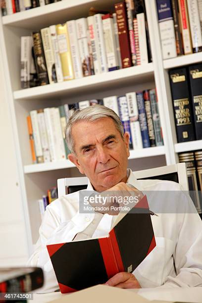 The Italian journalist Carlo Rossella poses with a book in his study Pavia 9th March 2012