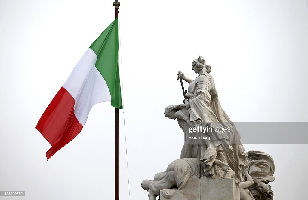 The Italian national flag flies near a monument to the unknown soldier in Rome, Italy, on Tuesday, Dec. 18, 2012. Italian Prime Minister Mario Monti, who is under pressure from euro-area and business leaders to enter the Italian election campaign, plans to quit once parliament passes his budget this week. Photographer: Alessia Pierdomenico/Bloomberg via Getty Images