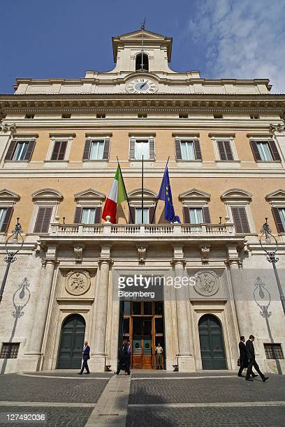 The Italian national flag left and the European Union flag fly above the main entrance to the Palazzo Montecitorio Italy's parliament building in...
