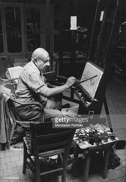 The Italian painter Giorgio de Chirico painting a stilllife in his studio Rome July 1967