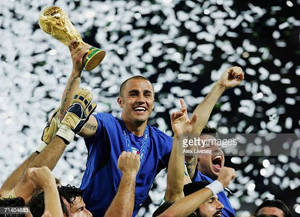 The Italian players celebrate as Fabio Cannavaro of Italy lifts the World Cup trophy aloft following victory in a penalty shootout at the end of the...