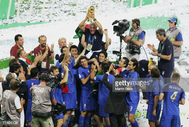 The Italian players celebrate as Marcello Lippi the coach of Italy lifts the World Cup trophy aloft following victory in a penalty shootout at the...
