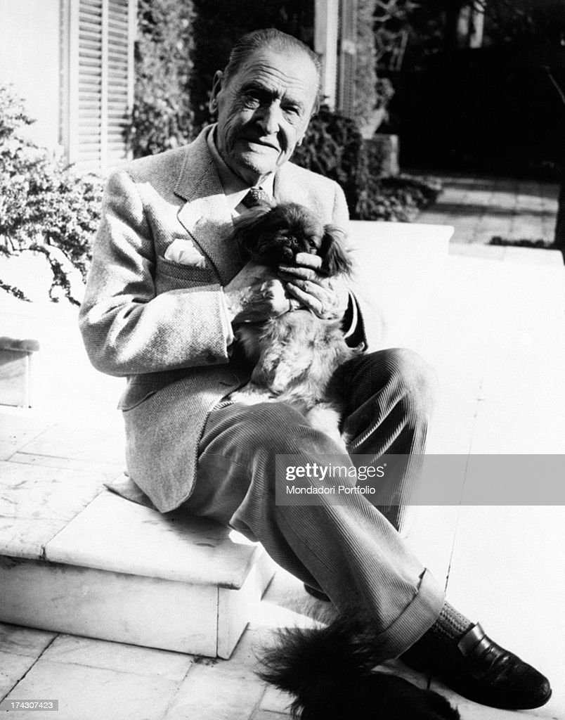 The Italian poet Giuseppe Ungaretti is seated on a low step in a courtyard holding his puppy a Pekinese and looking at the photographer with serenity...