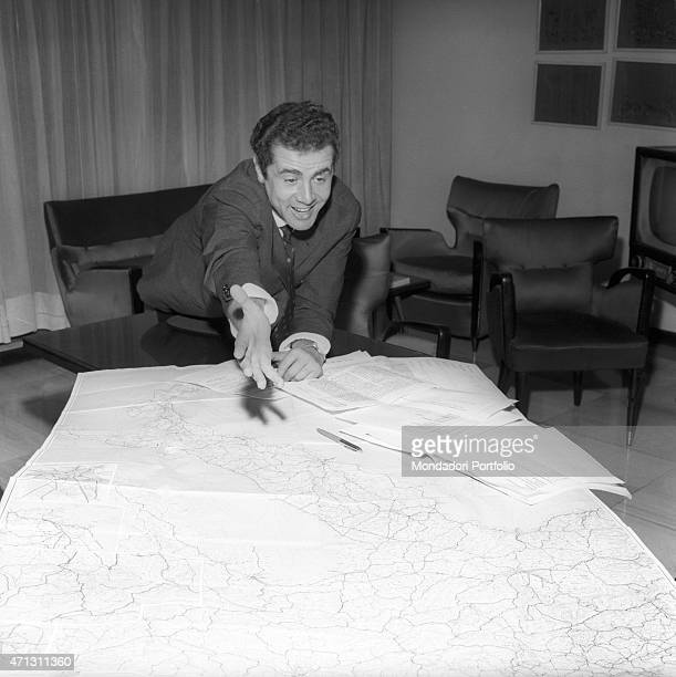 The Italian presenter Enzo Tortora smiles leaning on a table on which there is a map some sheets and a pen Milan 1967