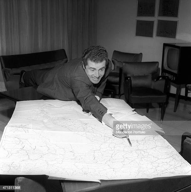 The Italian presenter Enzo Tortora stretches over a table to show with a pen a point on a map Milan 1967