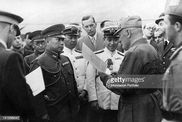 The Italian Prime Minister Benito Mussolini reading a message of the Japanese government before Colonel Giuseppe Casero Head of the Airforce Ministry...