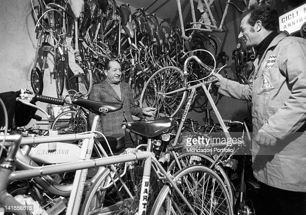 The Italian racing cyclist Gino Bartali meeting a mechanic among many bicycles Florence April 1975
