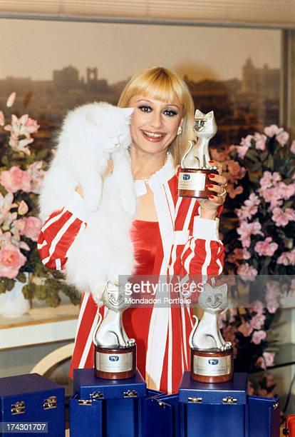 The Italian showgirl Raffaella Carrà artistic name Raffaella Maria Roberta Pelloni happily shows the photographer the three Telegatti awards she has...