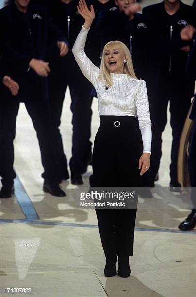 The Italian showgirl Raffaella Carrà born Raffaella Maria Roberta Pelloni stands waving her arm with an amused look on the stage of the TV programme...
